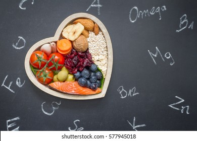 Healthy food in heart and chemical elements on blackboard