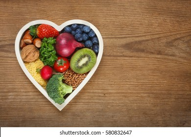 Healthy food in heart shaped bow. Food such as blueberries, red onion, strawberry, parsley leaves, hazelnuts, walnut, tomato. kiwi, millet, buckwheat, radish, broccoli.