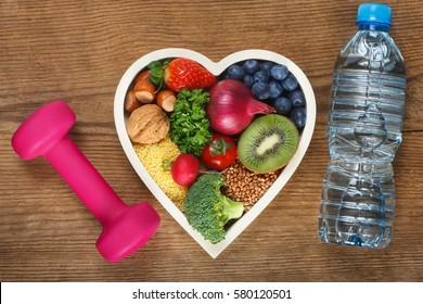 Healthy food in heart shaped bowl, bottle of water and dumbbell. Food such as blueberries, red onion, strawberry, parsley leaves, hazelnuts, walnut, tomato. kiwi, millet, buckwheat, radish, broccoli.