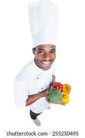 Healthy food is in his hands. Top view of cheerful young African chef in white uniform holding colorful vegetables while standing against white background
