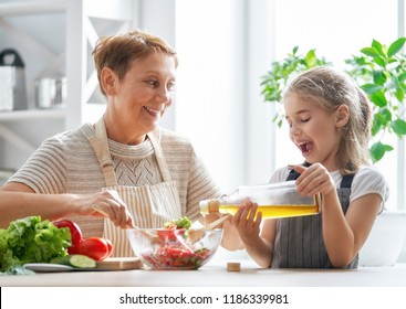 Healthy food at home. Happy family in the kitchen. Grandma and child are preparing the vegetables and fruit.
