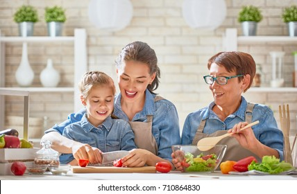 Healthy food at home. Happy family in the kitchen. Grandma, mother and child daughter are preparing the vegetables and fruit.