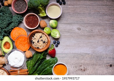 Healthy food ingredients. Above view side border on a wooden background. Copy space. Super food concept with green vegetables, berries, whole grains, seeds, spices and nutritious items.