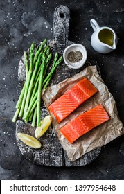 Healthy food ingredients for lunch - salmon fresh green asparagus on rustic chopping board on dark background, top view