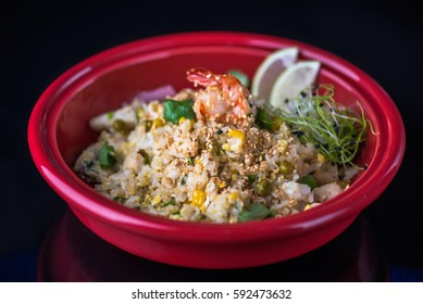 Healthy food in the Japanese style. Seafood with a red plate on a black background.