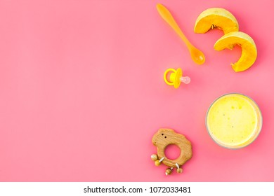 Healthy food for little baby. Puree with pumpkin near pacifier and toys on pink background top view copy space