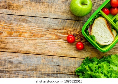 healthy food in lunchbox for dinner at school wooden table background