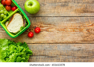healthy food in lunchbox for dinner at school wooden table background top view mockup