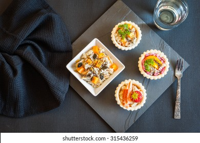 Healthy food. Mini tarts with various salads with Chia seeds. Quinoa salad with raw pumpkin, carrots and soy bean, Chia, pumpkin, sunflower and pine seeds, coconut sauce.