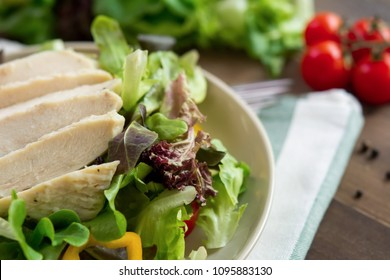 Healthy food, mix fresh vegetable salad toppped with skinless boiled chicken breast