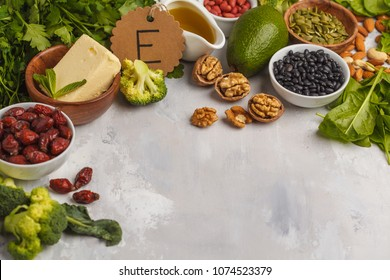 Healthy food nutrition dieting concept. Assortment of high vitamin E sources. Oil, nuts, avocado, butter, healthy fats, rose hips, parsley, seeds, spinach.
