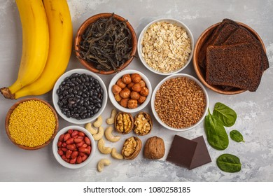 Healthy food nutrition dieting concept. Assortment of high magnesium sources, white background. Banana chocolate spinach, buckwheat, nuts, beans, oat.