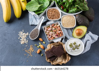 Healthy food nutrition dieting concept. Assortment of high magnesium sources. Banana chocolate spinach chard, avocado, buckwheat, sesame chia flax seeds, yogurt, nuts, beans oat