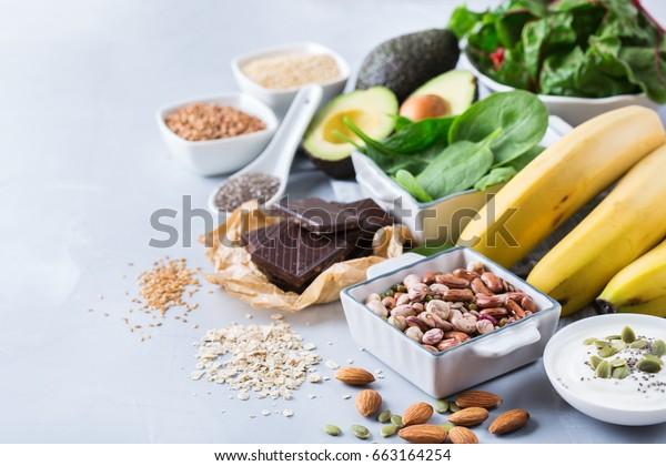 Gezonde voeding dieet dieet concept. Assortiment van hoge magnesiumbronnen. Banaan chocolade spinazie snijbiet, avocado, boekweit, sesam chia lijnzaad, yoghurt, noten, bonen haver. Ruimte achtergrond kopiëren
