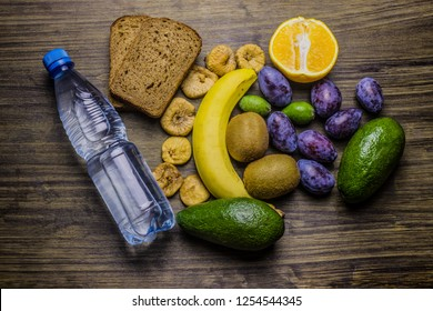 Healthy food on the table for a snack. A bottle of water. Slices of bread, banana, orange, kiwi, figs, feijoa and plums.