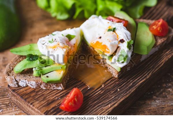 Nourriture saine, oeuf braconné et avocat sur pain rôti de seigle de blé entier. Mise au point sélective, vue en gros plan