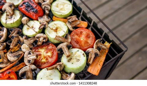 Healthy food preparing outdoors on summer or spring picnic. Grilled vegetables on grill on coals. Barbecue picnic on a meadow