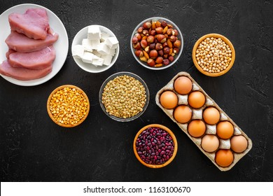 Healthy food. Products rich protein and fiber. Legumes, nuts, low-fat cheese, meet, eggs on black background top view copy space