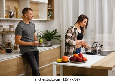 healthy food, proteins, proper nutrition, dieting, love, human relationships. fit couple having breakfast at home kitchen. woman cooking meals for her boyfriend