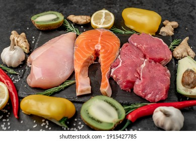 Healthy food - raw beef, salmon, chicken fillet, fruits and vegetables on a stone stone background.