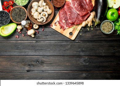 Healthy food. Raw beef with a variety of organic food and spices. On a wooden background.