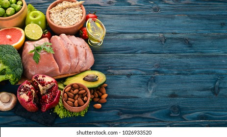 Healthy food. Raw meat, avocado, broccoli, fresh vegetables, nuts and fruits. On a wooden background. Top view. Copy space.