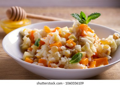 Healthy food: rice porridge with pumpkin, apples and raisins. Vegetarian or diet dish of rice and pumpkin good for breakfast