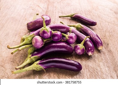 Healthy food round and long fresh organic raw purple brinjal or purple eggplant or aubergine  on wood table. (Selective focus).