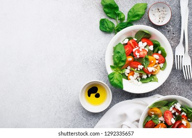 Healthy food. Salad of colored cherry tomatoes, cottage cheese, basil with olive oil, balsamic, sea salt, portioned black pepper. top view. On a gray dark background.