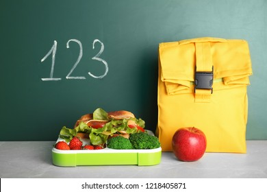 Healthy food for school child on table near chalkboard with written numbers