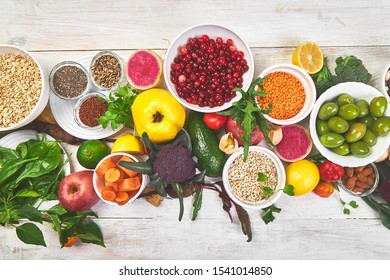 Healthy food selection, clean eating. Fruit, vegetable, seeds, superfood, cereals, leaf vegetable on white background, copy space top view