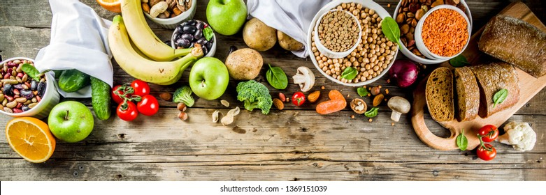 Healthy food. Selection of good carbohydrate sources, high fiber rich food. Low glycemic index diet. Fresh vegetables, fruits, cereals, legumes, nuts, greens. Wooden background copy space banner