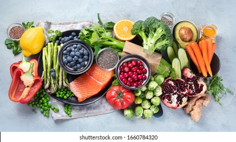 Healthy food selection on gray background. Detox and clean diet concept. Foods high in vitamins, minerals and antioxidants. Anti age foods. Top view - Shutterstock ID 1660784320