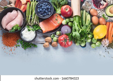 Healthy food selection on gray background. Detox and clean diet concept. Foods high in vitamins, minerals and antioxidants. Anti age foods. Top view with copy space