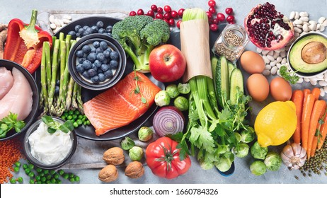 Healthy food selection on gray background. Detox and clean diet concept. Foods high in vitamins, minerals and antioxidants. Anti age foods. Top view