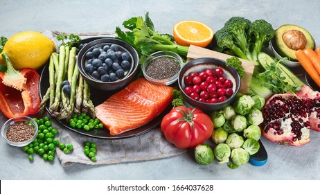 Healthy food selection on gray background. Detox and clean diet concept. Foods high in vitamins, minerals and antioxidants. Anti age foods.