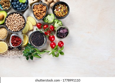 Healthy food selection on white wooden background . Fresh fruits , superfoods an vegatables . High in antioxidants, vitamins, minerals, fiber. Top view with copy space .
