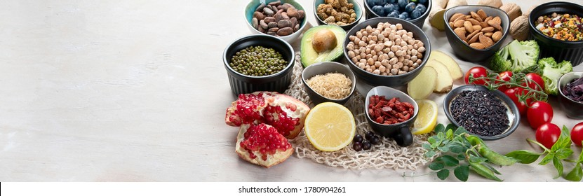 Healthy food selection on white wooden background . Fresh fruits , superfoods an vegatables . High in antioxidants, vitamins, minerals, fiber. Panorama with copy space .