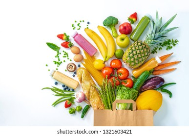 Healthy food selection. Shopping bag full of fresh vegetables and fruits isolated on white