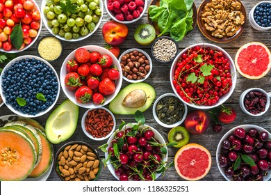 Healthy food selection. Super foods for breakfast, bowls with organic fresh fruits, assorted berries, seeds and nuts on table. Vegetarian diet concept.