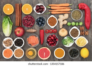 Healthy food to slow the ageing process concept including fruit, vegetables, fish, seeds, nuts, herbs, spices and pollen grain. Very high in antioxidants, anthocyanins, dietary fibre and vitamins.