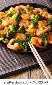 healthy food: stir fry shrimp with broccoli closeup on a plate. vertical