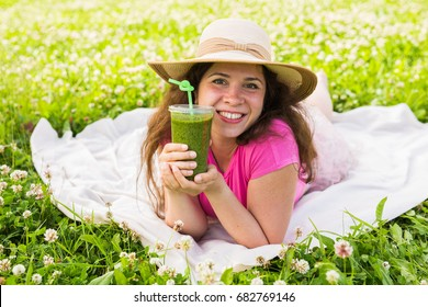 Healthy food, summer and people concept - Young woman have fun in the park and drink green smoothies at a picnic