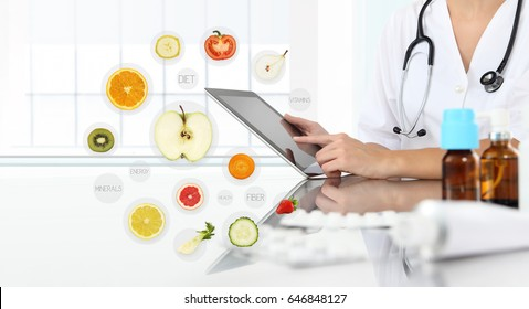healthy food supplements concept, Hand of nutritionist doctor touch digital tablet on symbols fruits background