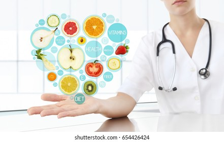 healthy food supplements concept, Hand of nutritionist doctor showing symbols fruits in heart shape