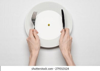 Healthy food theme: hands holding knife and fork on a plate with green peas on a white table top view