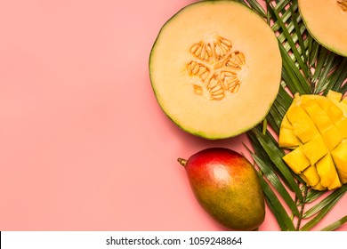 healthy food, tropical fruits, mango, melon on a monstera leaf with smoothies on a pink background, space for text flat lay