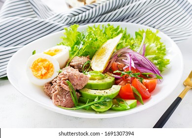 Healthy food. Tuna fish salad with eggs, lettuce, cherry tomatoes, avocado and red onions.  French cuisine.