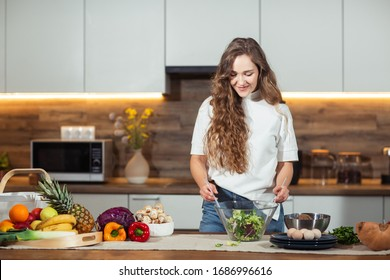 Healthy Food - Vegetable Salad. Diet. Dieting Concept. Young curly woman preparing vegetable salad in her kitchen. Healthy lifestyle concept, beautiful smiling woman mixed vegetable.