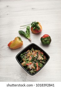 Healthy food: Vegetarian salad of vegetables, sesame, tomato, paprika, spinach, parsley, greens. Top view. Copy space.